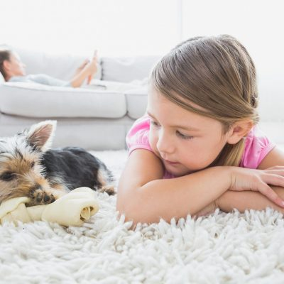 little girl and dog on carpet